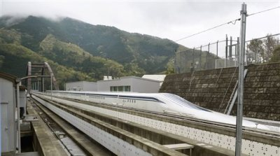 A Japanese maglev train that is the fastest passenger train in the world runs on the Maglev Test Line in Tsuru, about 80 kilometers (50 miles) west of Tokyo Tuesday, April 21, 2015. Operator JR Central said the train reached 603 kilometers per hour (375 miles per hour) in the test run on Tuesday, surpassing its previous record of 361 mph (581 kph) set in 2003. (Katsuya Miyagawa/Kyodo News via AP)