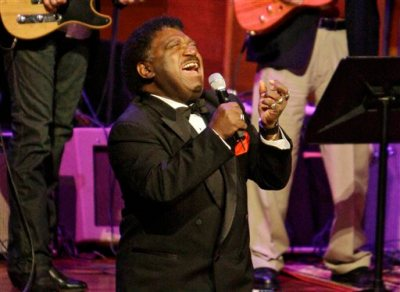 """In this Oct. 28, 2008 file photo, Percy Sledge kneels as he performs """"When a Man Loves a Woman"""" along with the Muscle Shoals Rhythm Section at the Musicians Hall of Fame awards show in Nashville, Tenn. Sledge, who recorded the classic 1966 soul ballad """"When a Man Loves a Woman,"""" died, Tuesday April 14, 2015. He was 74. (AP Photo/Mark Humphrey, File)"""