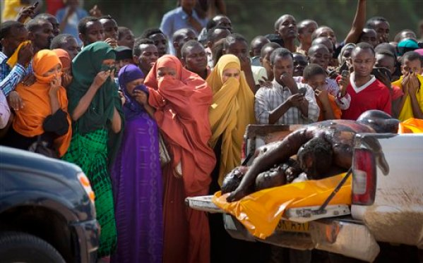 Women in the crowd cover their faces to protect against the smell as authorities display the bodies of the alleged attackers before about 2,000 people in a large open area in central Garissa, Kenya Saturday, April 4, 2015. Authorities displayed the bodies of the alleged attackers involved in the killings at Garissa University College on the bed of a pickup truck that drove slowly past the crowd, which broke into a run in pursuit. (AP Photo/Ben Curtis)