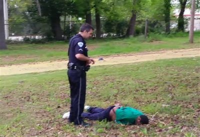 In this April 4, 2015, frame from video provided by attorney L. Chris Stewart representing the family of Walter Lamer Scott, Scott lies face down at the feet of City Patrolman Michael Thomas Slager, right, in North Charleston, S.C. Slager was charged with murder Tuesday, April 7, hours after law enforcement officials viewed the dramatic video that appears to show him shooting a fleeing Scott several times in the back. (AP Photo/Courtesy of L. Chris Stewart)