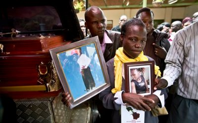 Mother Rosina Nafuna Wanda, center right, an unidentified relative, center left, and cousin Teresa Apiyo, standing behind, hold photographs of student Selpha Aoko Wanda, 21, who was killed in last week's Garissa attack, as they stand by a hearse ready to receive the body, at the Chiromo Funeral Parlour in Nairobi, Kenya Thursday, April 9, 2015. A week after the attack by extremist group al-Shabab on Garissa University College, relatives of the deceased continued their wait Thursday for the bodies to be released, hoping to be able to bury them. (AP Photo/Ben Curtis)