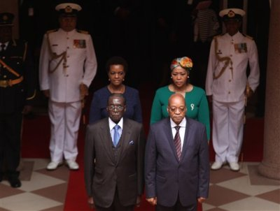 Zimbabwean President, Robert Mugabe, left, and his South African counterpart, Jacob Zuma, right, arrive for a welcoming ceremony at the government's Union Building in Pretoria, South Africa, Wednesday, April. 8, 2015. Mugabe is on a two-day state visit to the country. At rear are their wives, Grace Mugabe, left,  and Thobeka Zuma. (AP Photo/Denis Farrell)