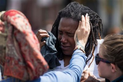 Shameeka Dream, of Baltimore is helped after being sprayed in the eyes with a crowd disbursement during a demonstration after an evening of riots following the funeral of Freddie Gray on Tuesday, April 28, 2015, in Baltimore. Gray died from spinal injuries about a week after he was arrested and transported in a Baltimore Police Department van. (AP Photo/Evan Vucci)