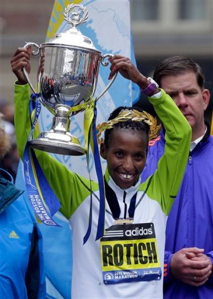 Caroline Rotich, of Kenya, lifts her trophy after winning the women's division of the Boston Marathon, Monday, April 20, 2015, in Boston. (AP Photo/Elise Amendola)