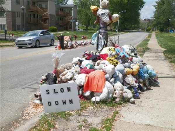 A car passes two makeshift memorials to Michael Brown Tuesday, May 5, 2015, near where the unarmed, black 18-year-old was shot and killed last August by white Ferguson, Missouri, Police Officer Darren Wilson. The 9-month-old shrine in the middle of the road, marking the spot were Brown fell dead, has been hallowed symbol of a new civil rights movement over race and policing _ and to others, now more of an eyesore and a road hazard. The city, Brown's family and a Washington-based mediator are grappling with the thorny question of whether to remove or replace it and risk further inflaming racial tensions. (AP Photo/Jim Salter).