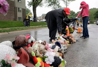 Volunteers Cheyenne Green, right, and Derrick Robinson help remove items left at a makeshift memorial to Michael Brown Wednesday, May 20, 2015, in Ferguson, Mo. The memorial that has marked the place where Brown was fatally shot by a police officer in August has been removed and will be replaced with a permanent plaque, Ferguson's Mayor James Knowles said Wednesday. (AP Photo/Jeff Roberson)