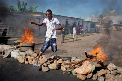 A civilian jumps over a burning barricade of rocks erected by residents to protect themselves from police, in a northern district of the capital Bujumbura, in Burundi Thursday, May 14, 2015. Gunfire and explosions rang out in Burundi's capital on Thursday as military forces backing an attempted coup against President Pierre Nkurunziza battled it out with forces loyal to the elected leader. (AP Photo/Erik Esbjornsson)