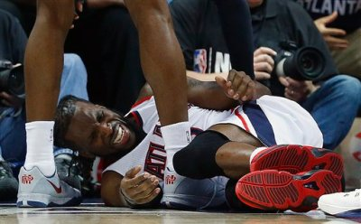 Atlanta Hawks forward DeMarre Carroll lies on the court as Atlanta Hawks forward Paul Millsap speaks after Carroll was injured against the Cleveland Cavaliers during the second half in Game 1 of the Eastern Conference finals of the NBA basketball playoffs, Wednesday, May 20, 2015, in Atlanta. (AP Photo/John Bazemore)