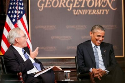"""President Barack Obama smiles as Washington Post Columnist E. J. Dionne speaks at the Catholic-Evangelical Leadership Summit on Overcoming Poverty at Gaston Hall at Georgetown University in Washington, Tuesday, May 12, 2015. The president said that """"it's a mistake"""" to think efforts to stamp out poverty have failed and the government is powerless to address it. (AP Photo/Andrew Harnik)"""