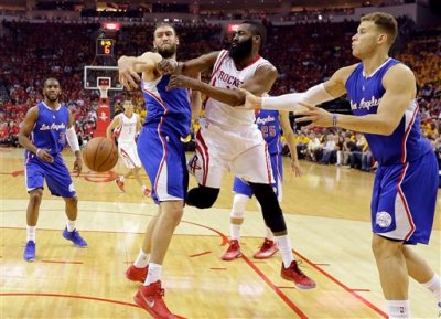 Houston Rockets' James Harden, center, is pressured by Los Angeles Clippers' Spencer Hawes (10) and Blake Griffin, right, during the first half in Game 5 of the NBA basketball Western Conference semifinals Tuesday, May 12, 2015, in Houston. (AP Photo/David J. Phillip)