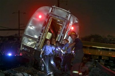 FILE - In this May 12, 2015 file photo, emergency personnel work the scene of a deadly train wreck in Philadelphia. An Amtrak train headed to New York City derailed and crashed in Philadelphia. Senate Democrats are demanding more money for Amtrak so the railroad can tackle a $21 billion backlog in repair and replacement projects. They say that backlog compromises safety and service. (AP Photo/ Joseph Kaczmarek)