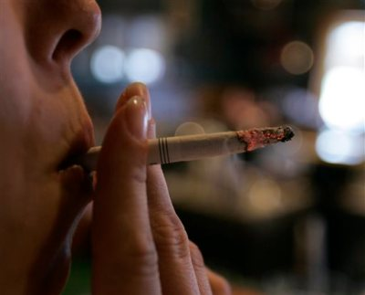 "In this Tuesday, June 3, 2008 file photo, an employee smokes a cigarette at a bar and restaurant in Harrisburg, Pa. In a study released Wednesday, May 13, 2015, smokers with $150 of their own money at stake were far more likely to quit than smokers who didn't have to wager their money to get cash rewards. ""A bit of a stick was much better than pure carrot,"" said the study's lead author, Dr. Scott Halpern of the University of Pennsylvania. But here's the catch: Few people were willing to bet on themselves. Nearly everyone who was offered the rewards-only option, though, signed up for a stop smoking program. (AP Photo/Carolyn Kaster)"
