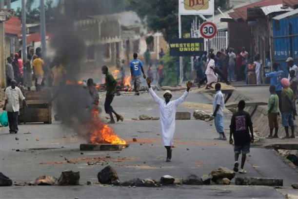 Protester stands by a burning barricade in the Musaga neighborhood of Bujumbura, Burundi, Thursday May 21, 2015. Protests continue against the  President's decision to seek a third term.  ( AP Photo/Jerome Delay)