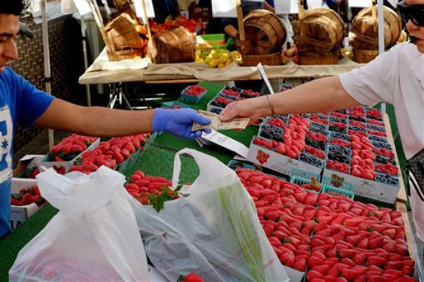 In this Friday, Feb. 6, 2015 file photo, a shopper pays for produce at a Farmers Market in downtown Los Angeles. Consumers have been uncharacteristically frugal, even as the country added jobs and a sharp drop in gas prices over the past year left them more money to spend. (AP Photo/Richard Vogel, File)