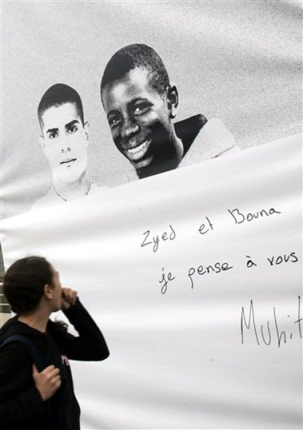 """In this Oct. 20, 2006 file photo, a resident walks past photos of Zyed Benna, left, and Bouna Traore who died after being electrocuted in a power substation while hiding from police on Oct. 27, 2005 in Clichy-Sous-Bois, outside Paris.  A French court has acquitted Monday, May 18, 2015 two police officers who were accused of contributing to the deaths of two teenagers in a blighted Paris suburb a decade ago. Poster reads: """"Zyed and Bouna, I will not forget you"""".   (AP Photo/Christophe Ena, File)"""