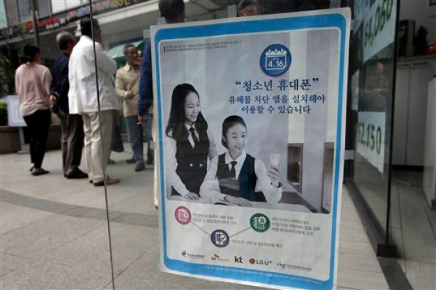 "A promotional banner of mobile apps that block harmful contents, is posted on the door at a mobile store in Seoul, South Korea, Friday, May 15, 2015. The banner reads: ""Young smartphone users, you must install apps that block harmful content."" ""Smart Sheriff"" app was funded by the South Korean government primarily to block access to pornography and other offensive content online. But its features go well beyond that. Smart Sheriff and at least 14 other apps allow parents to monitor how long their kids use their smartphones, how many times they use apps and which websites they visit. Some send a child's location data to parents and issue an alert when a child searches keywords such as ""suicide,"" ''pregnancy"" and ""bully"" or receives messages with those words. (AP Photo/Lee Jin-man)"