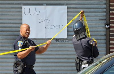 Officers put up tape Monday, May 4, 2015, in Baltimore. Lt. Col. Melvin Russell said police pursued a man who was spotted on surveillance cameras and appeared to be armed with a handgun. Police said the man was taken into custody after a brief chase, during which a gunshot was heard. (Amy Davis/The Baltimore Sun via AP)