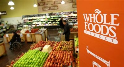 This March 27, 2014 photo shows shoppers in the produce section at the the Whole Foods Market in Woodmere Village, Ohio. Whole Foods reports quarterly financial results on Wednesday, May 6, 2015. (AP Photo/Tony Dejak)