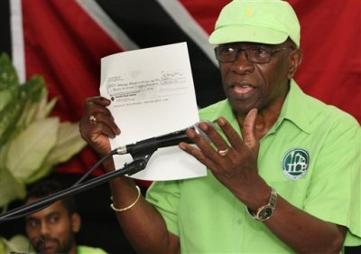 Former FIFA vice president Jack Warner hold a copy of a check while he speaks at a political rally in Marabella, Trinidad and Tobago, Wednesday, June 3, 2015. Warner made a televised address Wednesday night, saying he will prove a link between soccer's governing body and his nation's elections in 2010. Warner said he has documents and checks that link FIFA officials, including embattled President Sepp Blatter, to the 2010 election in Trinidad and Tobago. (AP Photo/Anthony Harris)