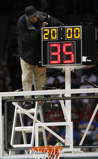 In this March 19, 2010, file photo, a technician adjusts a shot clock after it malfunctioned and delayed the start of the California against Louisville NCAA first-round college basketball game in Jacksonville, Fla. On Monday, June 8, 2015, the NCAA's Playing Rules Oversight Panel officially approved that men's college basketball teams will play with a quicker shot clock (30 seconds instead of 35 seconds) and fewer timeouts next season which were made last month by the basketball rules committee. Teams will have one fewer second-half timeout, and if either team calls a timeout within 30 seconds of a media timeout, it would count as the scheduled break. (AP Photo/Steve Helber, File)