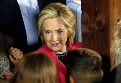 """In this June 15, 2015 file photo, Democratic presidential candidate Hillary Rodham Clinton shakes hands after speaking inside a barn as it rained in Concord, N.H. Republican Jeb Bush and Clinton are asking donors to write the checks to get their campaigns started. Yet these """"new"""" candidates have been fueling their presidential ambitions for months—years, in Clinton's case—thanks to outside groups that will continue serving as big-money bank accounts throughout the race. In the 2016 presidential field, creative financing abounds. (AP Photo/Jim Cole, File)"""