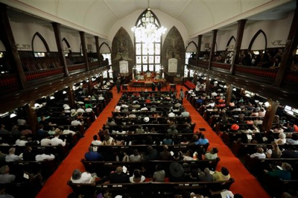 Parishioners sit at the Emanuel A.M.E. Church four days after a mass shooting that claimed the lives of it's pastor and eight others on Sunday, June 21, 2015, in Charleston, S.C. (AP Photo/David Goldman, Pool)