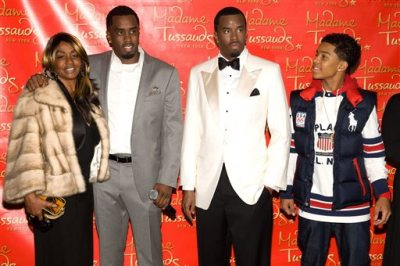 """In this Dec. 15, 2009 file photo, Sean Combs, second left, is joined by his mother Janice, left, and son Justin, right, as he unveils his wax figure at Madam Tussauds in New York. Sean """"Diddy"""" Combs was defending himself in an incident at the University of California, Los Angeles, that led to his arrest, a representative the hip-hop mogul's company said Tuesday, June 23, 2015. Diddy was arrested Monday for an alleged assault involving a weight-room kettlebell at the athletic facilities of UCLA, where his son, Justin Combs, plays football, a university statement said. (AP Photo/Charles Sykes, File)"""