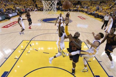 Cleveland Cavaliers forward LeBron James (23) shoots between Golden State Warriors forward Draymond Green, left, and guard Stephen Curry during the second half of Game 2 of basketball's NBA Finals in Oakland, Calif., Sunday, June 7, 2015. The Cavaliers won 95-93 in overtime. (Ezra Shaw/Getty Images Pool via AP)