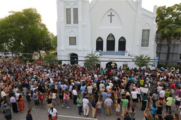 Hundreds of people attend a sidewalk memorial to the shooting victims in front of Emanuel AME Church, Friday, June 19, 2015, in Charleston, S.C. (Curtis Compton/Atlanta Journal-Constitution via AP)  MARIETTA DAILY OUT; GWINNETT DAILY POST OUT; LOCAL TELEVISION OUT; WXIA-TV OUT; WGCL-TV OUT