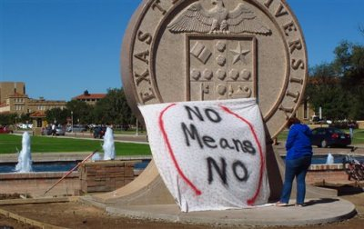 """In this Wednesday, Oct. 1, 2014 file photo, Texas Tech freshman Regan Elder helps drape a bed sheet with the message """"No Means No"""" over the university's seal at the Lubbock, Texas campus to protest what students say is a """"rape culture"""" on campus. A picture of a banner at a Sept. 20 Phi Delta Theta fraternity gathering, briefly posted online, read, """"No Means Yes,"""" followed by a graphic sexual remark. A study by the Canadian Institutes of Health Research and the University of Windsor published on Wednesday, June 10, 2015 found that a program that taught college women ways to prevent sexual assault cut in half the chances they would be raped over the next year. It was the first large, scientific test of resistance training, and the strong results should spur more universities to offer it, experts say. (AP Photo/Betsy Blaney)"""