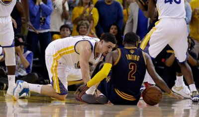 Cleveland Cavaliers guard Kyrie Irving (2) tries to control the ball next to Golden State Warriors guard Klay Thompson during overtime of Game 1 of basketball's NBA Finals in Oakland, Calif., Thursday, June 4, 2015. Irving left the game with an injury right after this play. (AP Photo/Ben Margot)