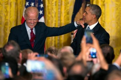 Vice President Joe Biden, left, and President Barack Obama react after a heckler was removed from the East Room of the White House during remarks at a reception to celebrate LGBT Pride Month, on Wednesday, June 24, 2015, in Washington. (AP Photo/Evan Vucci)