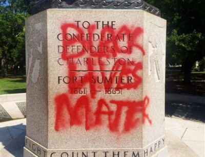 "A statue memorializing the Confederacy is spray-painted with the message ""Black Lives Matter"" several days after a shooting at a historic black church Sunday, June 21, 2015, in Charleston, S.C. Police spokesman Charles Francis said city workers used a tarp to cover up the graffiti marking the stone pedestal beneath the statue. He said he didn't know when the graffiti was spray-painted there, but said it would be cleaned off. (AP Photo/WCSC-TV, Philip Weiss)"