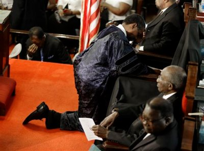 """In this June 21, 2015, file photo, Rev. Norvel Goff prays at the empty seat of the Rev. Clementa Pinckney at the Emanuel A.M.E. Church four days after a mass shooting that claimed the lives of Pinckney and eight others in Charleston, S.C. The 65-year-old Goff was named interim leader of the historic church called """"Mother Emanuel"""" at one of the lowest points in its nearly 200-year history. But the Georgetown, South Carolina, native says the church won't dwell on the past.(AP Photo/David Goldman, Pool, File)"""