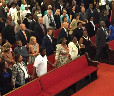 """U.S. Vice President Joe Biden, center, with son and daughter-in-law Hunter and Kathleen Biden, to his right, sing """"We Shall Overcome"""" while joining hands with Emanuel AME Church members Sunday, June 28, 2015 in Charleston, S.C. Biden delivered a short speech and said he was there to stand in solidarity with the church and families of the nine people who were killed June 17.  (Melissa Boughton/The Post and Courier via AP)"""