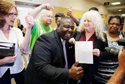 Marq Lewis, of We the People, and attorney Laurie Phillips celebrate with a court ruling after a hearing about the petition seeking a grand jury investigation into Sheriff Stanley Glanz at the Tulsa County Courthouse, Tuesday, June 30, 2015, in Tulsa, Okla. A grand jury should review operations at an Oklahoma sheriff's office that sent onto the streets a 73-year-old reserve deputy who shot and killed an unarmed and restrained suspect, a judge ruled Tuesday. (Mike Simons/Tulsa World via AP)