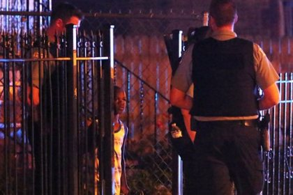 A young boy watches as police investigate the scene where a 7-year-old boy was killed and a 26-year-old woman was injured in a shooting in the the 1100 block of North Harding Avenue during the early morning hours Sunday, July 5, 2015 in the Humboldt Park neighborhood of Chicago. Police say there were at least seven deaths over the July 4 weekend that ended with more than 50 people shot in three dozen separate incidents. (Anthony Souffle/Chicago Tribune via AP)