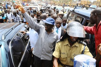 In this Wednesday, March 21, 2012 file photo, opposition leader Kizza Besigye, center, gestures the party sign before being arrested for holding a rally in Kampala, Uganda. Ugandan police said Thursday, July 9, 2015 that they have detained former Prime Minister Amama Mbabazi, who last month announced he would seek the presidency in elections next year, and also detained opposition leader Kizza Besigye, who planned to address two rallies, according to his aide. (AP Photo/Stephen Wandera, File)