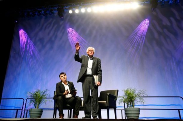 Democratic presidential candidate Sen. Bernie Sanders, I-Vt., tries to speak as he is shouted down by protesters as moderator Jose Vargas watches at left, Saturday, July 18, 2015, at a Netroots Nation town hall meeting in Phoenix. (AP Photo/Ross D. Franklin)