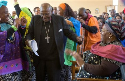 In this Saturday, July 4, 2015 file photo  retired Anglican Archbishop Desmond Tutu, centre, breaks into dance after renewing his wedding vows to his wife of 60 years, Leah, right, during a service in Soweto, Johannesburg. Tutu will spend a second night in a Cape Town hospital, Wednesday July 15, 2015, as he continues to receive treatment for a persistent infection. (AP Photo/File)