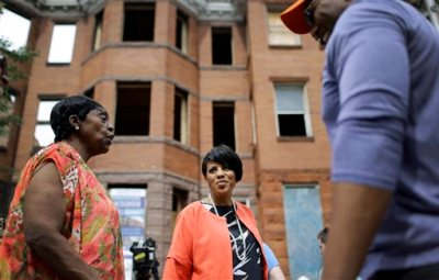 In this photo taken Tuesday, July 21, 2015, Baltimore Mayor Stephanie Rawlings-Blake, center, speaks with residents outside of vacant homes before a ceremony to kick off their restoration in Baltimore. For many in Baltimore, the memory of April's riots - and the mayor's handling of the unrest - is still fresh. After firing embattled police commissioner Anthony Batts, who bore the brunt of public outrage, Rawlings-Blake remains the primary figure head of a city that is still reeling from the damage it suffered. (AP Photo/Patrick Semansky)
