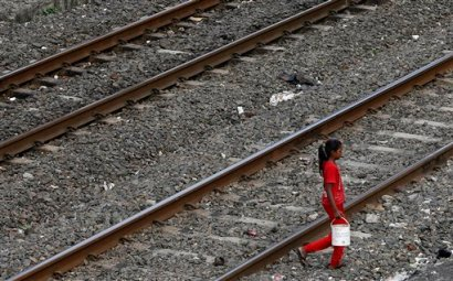 An Indian girl holds a can filled with water and walks past railway tracks to defecate in the open in Mumbai, India, Tuesday, June 30, 2015. Toilets are taken for granted in the industrialized West, but still are a luxury for a third of the world's people who have no access to them, according to a report by the World Health Organization and UNICEF released Tuesday. India is by far the worst culprit, with more than 640 million people defecating in the open, and not necessarily due to a lack of facilities. (AP Photo/Rajanish Kakade)