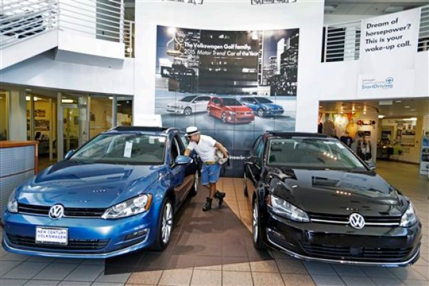 In this Thursday, July 2, 2015, photo, customer Armando Barillas checks the interior of a vehicle for sale at the New Century Volkswagen dealership in Glendale, Calif. Volkswagen overtook Toyota in global vehicle sales for January-June, the first time the German automaker has come out top in the intensely competitive tallies. (AP Photo/Damian Dovarganes)