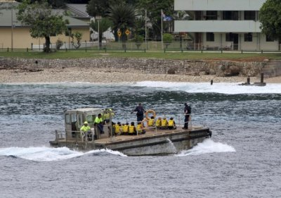 On April 14, 2013, a group of Vietnamese asylum seekers are taken by barge to a jetty on Australia's Christmas Island. (AP Photo)