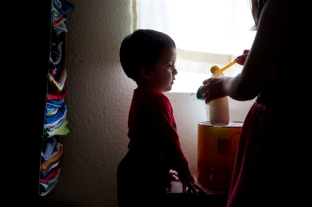 In this Monday, June 8, 2015 photo, 1-year-old Joshua Tinoco watches as his mother, Dunia Bueso, a 18-year-old Honduran who won the right to seek permanent residency under a U.S. program for abused and abandoned children, fills a bottle with baby formula at their relative's home in Los Angeles. At a brief hearing, a government lawyer tells the teenage mother that her son is an immigration enforcement priority for the United States and should be sent back to his native Honduras even though she is being allowed to stay and seek a green card. (AP Photo/Jae C. Hong)