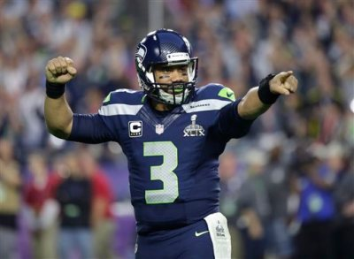 In this Feb. 1, 2015, file photo, Seattle Seahawks quarterback Russell Wilson celebrates after throwing a touchdown pass during the first half of NFL Super Bowl XLIX football game against the New England Patriots in Glendale, Ariz. Russell Wilson is sticking around with the Seattle Seahawks.  Wilson tweeted Friday morning, July 31, 2015, that he has agreed to a four-year contract extension with the Seahawks, keeping him with the franchise that took him in the third round of the 2012 draft and watched him become one of the most successful young quarterbacks in NFL history. (AP Photo/David Goldman)