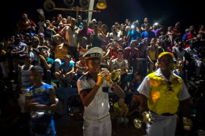 In this July 25, 2015 photo, a reveler plays the trumpet at the start of a carnival parade in Santiago, Cuba. Along with the new oceanfront Malecon and the restoration of homes in the city's historic center, the Cuban government has built a new theater and an artisanal brewpub as part of a broader reconstruction and improvement effort that began after Hurricane Sandy devastated the city in 2012. (AP Photo/Ramon Espinosa)
