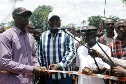 In this photo taken Friday, Aug. 14, 2015, Sierra Leone President Ernest Bai Koroma, centre, cuts a tape to release people from quarantine in the village of Massessehbeh on the outskirts of Freetown, Sierra Leone.  Five months after a man traveled to his home village for festivities marking the end of Ramadan, and died suddenly from Ebola, but now President Koroma came to cut down the fencing to mark the formal end of Sierra Leone's largest remaining Ebola quarantine.  (AP Photo/Sunday Alamba)