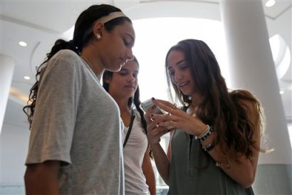 In this July 27, 2015, photo, Giulia Pugliese, 15, right, posts a picture to Snapchat while her friend Isabella Cimato, 17, left, and her cousin Arianna Schaden, 14, look on at Roosevelt Field shopping mall in Garden City, N.Y. Teens aren't roaming around at the mall for kicks during back-to-school. They're researching the looks they want online and follow popular hashtags on social media so they can piece together looks before they get there. (AP Photo/Seth Wenig)