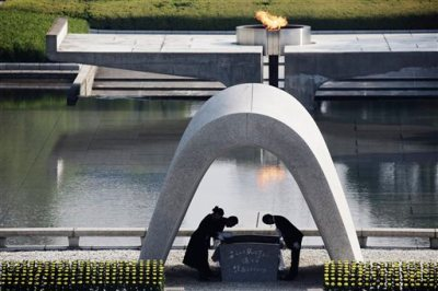 Kazumi Matsui, right,  mayor of Hiroshima, and the family of the deceased bow before they place the victims list of the Atomic Bomb at Hiroshima Memorial Cenotaph during the ceremony to mark the 70th anniversary of the bombing at the Hiroshima Peace Memorial Park in Hiroshima, western Japan Thursday, Aug. 6, 2015. (AP Photo/Eugene Hoshiko)